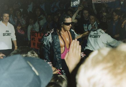 For his entrances, Hart often wore a leather jacket with shoulder tassels (epaulets), Mylar wrap-around (originally silver, later pink) sunglasses and bright pink attire Bret Hart entrance.jpg
