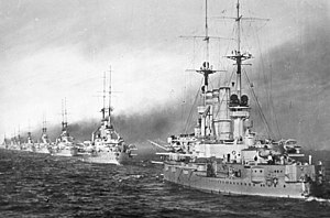 A long line of large, light gray warships sail through calm waters, each belching thick black smoke