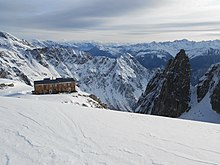 mountain refuge overlooking snow-covered Swiss mountains