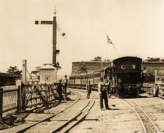 Cape Town Railway & Dock 2-4-0T - A 2-4-0T locomotive entering Cape Town station on dual gauge track at the old Strand street level crossing, with the Castle of Good Hope in the background, c. 1880