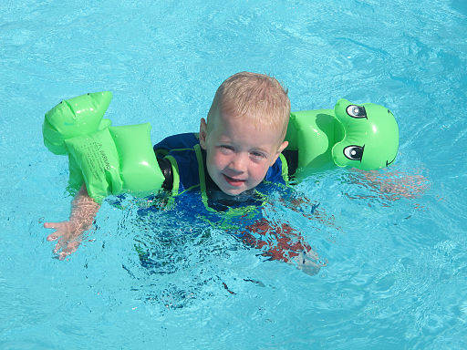 Child wearing green floaties