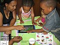 Children using tablets at City of Joburg libraries to draw art with parents.jpg