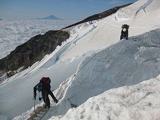 Hazards of outdoor recreation - Crossing a crevasse on Mt Rainier, USA.