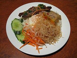 Cơm tấm - Cơm tấm with grilled pork, shredded pork, pork skin, fried egg, pork meatloaf, pickled carrot, and sliced cucumber