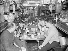 Around 15 men are drinking from white mugs at a table in a narrow compartment. They are surrounded by bunk-beds and machinery. The space is cramped and the men are packed closely together.