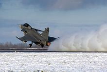 Three-quarter hind view of grey jet aircraft taking off in snowy environment.  Its engine is kicking up snow on the ground