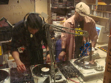 Two hip hop DJs creating new music by mixing tracks from multiple record players. Pictured are DJ Hypnotize (left) and Baby Cee (right). DJ Hypnotize and Baby Cee.jpg