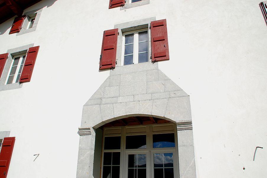 Façade de maison. Texte écrit: 'Etcharteco semiac etche berria eguin 1855 etche hundaco familia jaincoak benefica dezala' (Maison neuve construite par le fils d'Etcharté en 1855 afin que Dieu protège la famille de cette maison).
