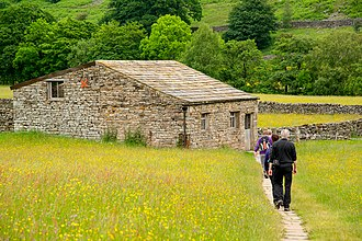 North Yorkshire - Hikers at a traditional field barn in Muker, North Yorkshire