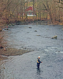 A wide muddy stream with some rapids surrounded by woods with bare trees and a red structure visible through them behind a bend at the rear. At the left are two men knee-deep in the water, holding fishing rods with a colored line attached