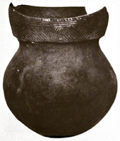 Black and white photo of a ceramic pot with a round bottom, short neck, and a rim decorated with geometric line patterns. The rim is broken in the rear.