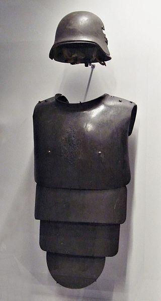 الحرب ال - الحرب العالميه الاولى 320px-German_helmet_and_frontal_armoured_plate_for_trench_warfare_1916