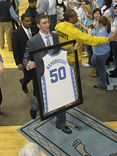 A young Caucasian man with short hair is walking toward a basketball arena's tunnel entrance holding a framed replica of his college basketball jersey. He is wearing a suit and baby blue tie.