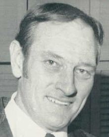 Posed black and white head-shot photograph of Gamble wearing a sport coat and tie