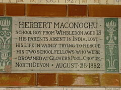 "A tablet formed of six standard sized tiles, bordered by green flowers in the style of the Arts and Crafts movement. The tablet reads ""Herbert Maconoghu schoolboy from Wimbledon aged 13. His parents absent in India, los his life in vainly trying to rescue his two school fellows who were drowned at Glovers Pool, Croyde, North Devon August 28, 1882""."