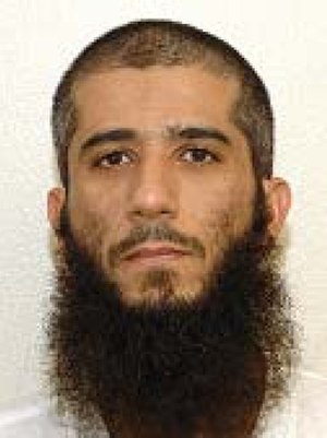 "Faiz Mohammed Ahmed Al Kandari - Faez Mohammed Ahmed al-Kandari's official Guantanamo identity portrait, showing him wearing the white uniform issued to ""compliant"" captives."
