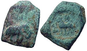 Coinage of India - Ancient Indian Coin from Taxila, India, dating back to the 304-232 BC. One of the earliest style coins from ancient India. On the obverse, it has an Elephant advancing right, and on the reverse, a Lion standing left, with hill to left and swastika above.