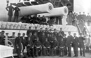 Italia-class ironclad - Admiral Canevaro and the officers of Italia pose under a pair of her 17-inch guns