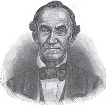 A man with receding black hair, a high-collared white shirt, and a black jacket and bowtie