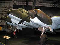 A color photograph of the front section of a twin engine propeller aircraft in a museum, shown in semi profile, viewed from the front left. The aircraft is painted green and light blue. Antennas are protruding from the nose of the aircraft.