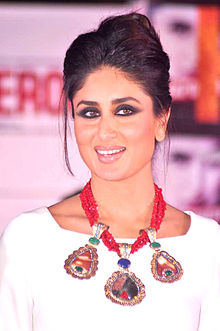 A young Indian woman clad in a white dress with her hair pulled back. A red necklace is hung around her neck, coming up to her breasts. She is looking to the right and smiling.