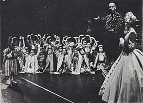 Black and white photo of a theatrical scene: a middle-aged man with a shaved head and imposing presence has his right arm extended to introduce a group of children in Asian dress to a woman in a crinoline dress and bonnet in the foreground at right, who is partially turned upstage. The children are mostly kneeling and have their arms raised in greeting; one child (probably Crown Prince Chulalongkorn) stands and bows.
