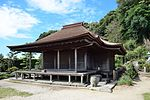 A wooden building with a wide front veranda.