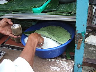 Kue putu - Bamboo tube being filled with rice flour