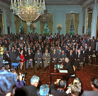United States President Lyndon B. Johnson speaks to a television camera at the signing of the Civil Rights Act in 1964 LBJ Civil Rights Act crowd.jpg