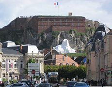 photographie la statue du Lion de Belfort bâchée avant son inauguration avec au premier plan la Vieille Ville et à l'arrière-plan la citadelle et sa caserne