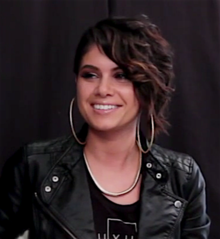 Still image of a woman looking away from the camera and smiling with an undercut hairstyle; wearing large hoop earrings, a black top, a thick necklace and a leather jacket.