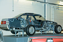 Sedan cutaway on museum display, showing trunk space, chassis, cabin, and engine bay. The aft emblem says 'Lexus'.