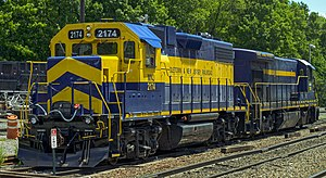 "A blue and gold diesel locomotive with ""2174"" on it in several locations and ""Middletown & New Jersey"" on the side sits on a railroad track, seen from its front left. On its right, facing the opposite direction, is a mostly blue locomotive of a different model with ""East Penn Railways"" written on it in gold"