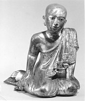 Wooden sculpture of monk sitting in a mermaid pose, reclining
