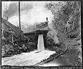Man standing on cofferdam pipe discharge, Masonry Dam, April 16, 1912 (SPWS 49).jpg