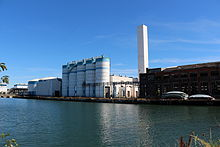 Five silos sit on a dock across the water, along with an old warehouse