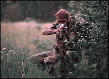 A young man with sandy blond hair, wearing brown and green Rhodesian-pattern military camouflage and a mesh scarf around his head, squats behind the cover of a large bush as he takes aim with a camouflaged FN FAL battle rifle. He is carrying a large backpack and has liberally applied dark camouflage cream to his skin.