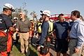 Michael Chertoff shakes hands with FEMA Urban Search and Rescue member, while Michael Brown speaks to another.jpg