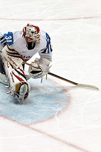 a goaltender in a blue and white uniform looks to his left as he stretches his legs