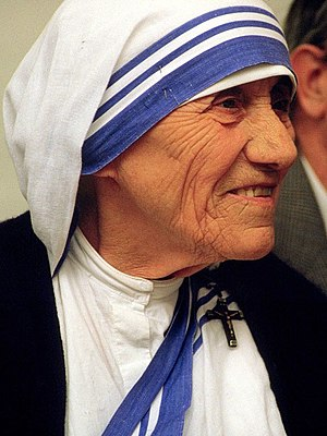 An image of Mother Teresa wearing a white head covering with blue stripes