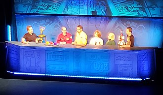Mystery Science Theater 3000 - The cast of the 30th Anniversary Live Tour, from left: Grant Baciocco (controlling Crow T. Robot), Joel Hodgson, Jonah Ray, Deana Rooney, Rebecca Hanson, and Tim Ryder (controlling Tom Servo)