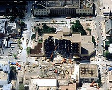 An overhead view shows the Alfred P. Murrah building, half of it destroyed from the bomb's blast, near the building are various rescue vehicles and cranes. Some damage is visible to nearby buildings.