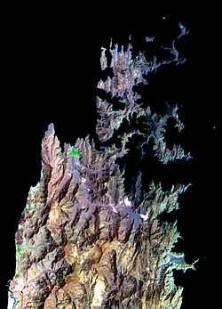 The peninsula as seen from space. Al-Khasab to the north (top) shown in green, is contrasted between the more subtle rainbow tones of the surrounding rock in this false-colour image. The term Khasab refers to the fertility of the soil.