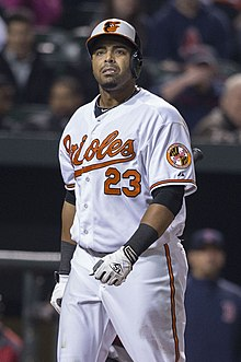 "A man wearing a white baseball uniform with ""Orioles"" and the number 23 written in orange on the chest"