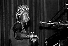 Head and torso of black woman at a piano in front of a microphone wearing a flowered kerchief in her hair