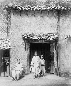 One Arab man and two Arab children in front of Kabyle house.jpg