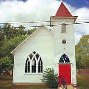 A white church with red doors and stained glass