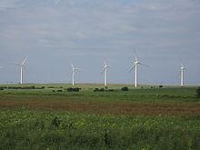 Une zone de champs verts plats avec cinq éoliennes d'un blanc éclatant se détachant de l'arrière-plan d'un ciel bleu.