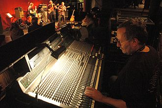 Mixing console - An audio engineer adjusts a mixer while doing live sound for a band.