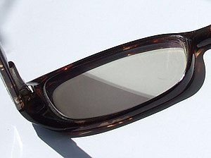 Photochromism - A photochromic eyeglass lens, after exposure to sunlight while part of the lens remained covered by paper.